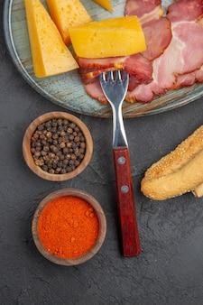 Verticale weergave van heerlijke worst en kaasplak op een blauwe plaat, paprika's op een donkere achtergrond