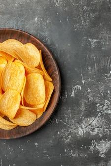 Verticale weergave van heerlijke zelfgemaakte aardappelchips op een bruine plaat op grijze achtergrond