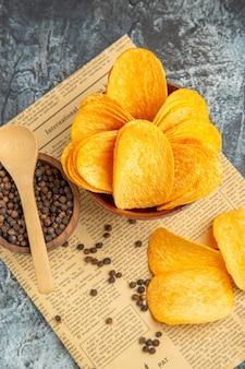 Verticale weergave van heerlijke zelfgemaakte chips en peper kom met lepel op krant op grijze achtergrond
