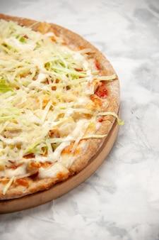 Verticale weergave van heerlijke zelfgemaakte veganistische pizza op gekleurd wit oppervlak
