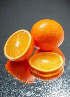Verticale weergave van hele gesneden verse sinaasappelen die op een donkere achtergrond met vrije ruimte staan