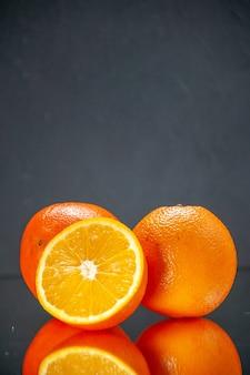 Verticale weergave van hele gesneden verse sinaasappels die naast elkaar staan op licht op een zwarte achtergrond met vrije ruimte