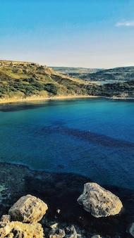 Verticale weergave van het adembenemende uitzicht op golden bay beach in mellieha, malta, vastgelegd op een zonnige dag