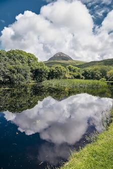 Verticale weergave van het connemara national park in mweelin, ierland onder een bewolkte blauwe hemel