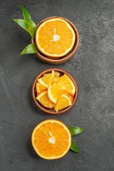 Verticale weergave van in tweeën gesneden gesneden op stukken verse citroenen bladeren en bloemen op zwarte tafel