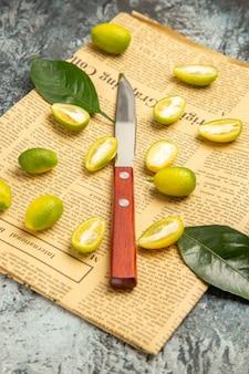 Verticale weergave van in tweeën gesneden verse kumquats op kranten op grijze achtergrondbeelden