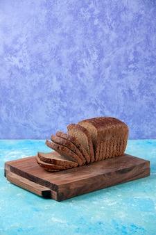 Verticale weergave van in tweeën gesneden zwarte sneetjes brood op houten planken op een lichte ijsblauwe patroonachtergrond