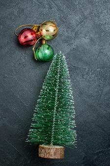 Verticale weergave van kerstboom en decoratieaccessoires aan de linkerkant op zwarte achtergrond