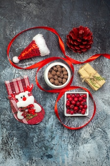 Verticale weergave van kerstman hoed en cornel chocolade nieuwjaarssok rode conifer kegel cadeau op donkere ondergrond