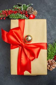 Verticale weergave van kerstmis achtergrond met prachtige geschenken met boogvormig lint en fir takken decoratie accessoires op een donkere tafel