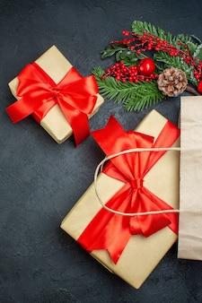 Verticale weergave van kerstsfeer met mooie geschenken en fir takken conifer kegel op donkere achtergrond