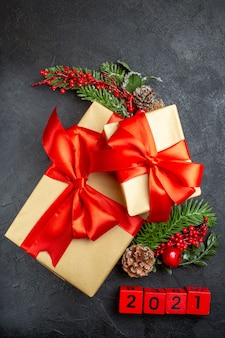 Verticale weergave van kerstsfeer met mooie geschenken met boogvormig lint en fir takken decoratie accessoires nummers op een donkere achtergrond