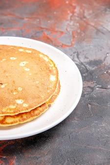 Verticale weergave van klassieke amerikaanse karnemelk pannenkoeken op witte plaat op gemengde kleur