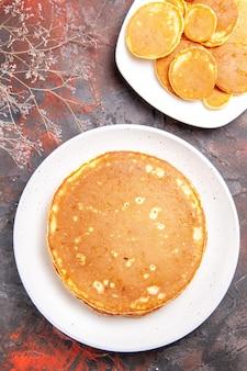 Verticale weergave van klassieke amerikaanse zelfgemaakte pannenkoeken op witte platen op gemengde kleurentafel