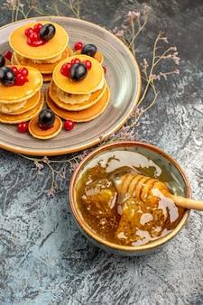Verticale weergave van klassieke fruitpannekoeken en honing in een kom