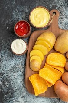 Verticale weergave van knapperige chips en ongekookte aardappelen op houten snijplank en mayonaise en ketchup op grijze tafel
