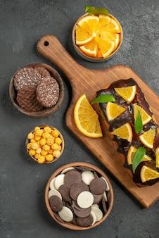Verticale weergave van lekkere taarten gesneden citroenen met koekjes op snijplank op donkere tafel
