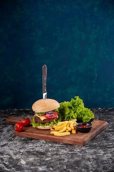 Verticale weergave van mes in vlees sandwich en frietjes tomaten met stam peper op houten bord ketchup op donkerblauw oppervlak