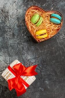 Verticale weergave van mooie geschenkdoos vastgebonden met rood lint en heerlijke macarons op ijzige donkere achtergrond