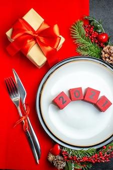 Verticale weergave van nieuwjaar achtergrond met getallen op diner plaat bestek set decoratie accessoires fir takken naast een geschenk op een rood servet