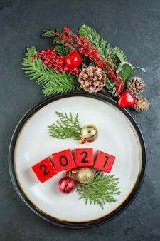Verticale weergave van nummers decoratie accessoires op een plaat fir takken naaldboom kegel op donkere achtergrond