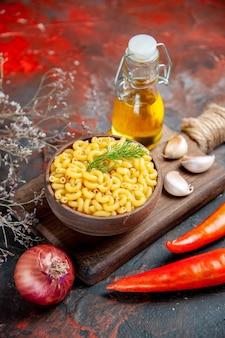 Verticale weergave van ongekookte pasta's in een bruine kom en knoflook op houten snijplank peper citroen ui op gemengde kleur achtergrond