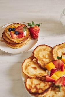 Verticale weergave van pannenkoeken met fruit op de top