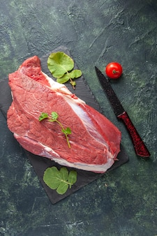 Verticale weergave van rauw vers rood vlees en groenten op snijplank mes tomaat op groen zwart mix kleuren achtergrond
