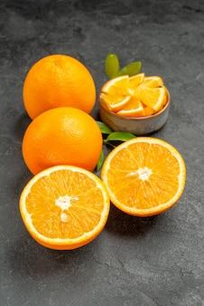 Verticale weergave van reeks gele hele en gesneden citroenen op donkere achtergrond