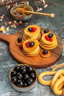 Verticale weergave van ringvormige koekjes fruit pannenkoeken honing in een kom en zwarte kersen op grijze tafel