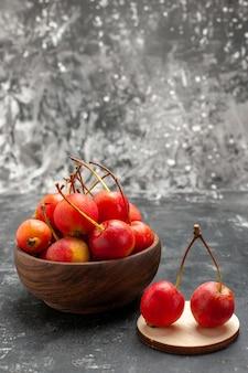 Verticale weergave van rode cheries in een bruine kom en op klein houten dienblad op grijs