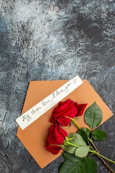 Verticale weergave van rode rozen en envelop met liefdesbrief op ijzige donkere achtergrond