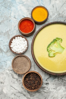Verticale weergave van romige broccolisoep in een bruine kom en verschillende kruiden op grijze achtergrond