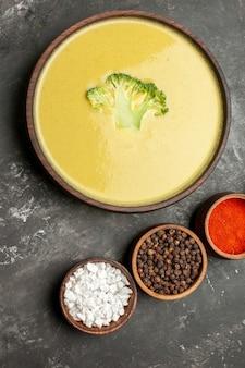Verticale weergave van romige broccolisoep in een bruine kom en verschillende kruiden op grijze tafel