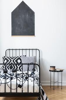 Verticale weergave van schoolbord aan de muur van tieners slaapkamer met zwart-wit patroon beddengoed op een metalen bed, echte foto met mockup