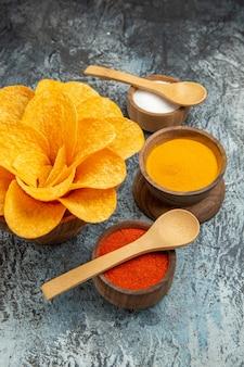 Verticale weergave van smakelijke aardappelchips ingericht als bloemvormige verschillende kruiden met lepels erop op grijze tafel