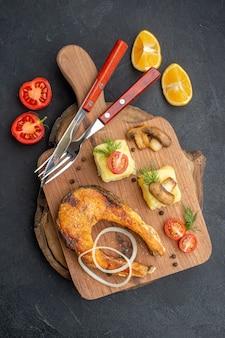 Verticale weergave van smakelijke gebakken vis en champignons tomaten groenen op snijplank bestekset peper op zwarte ondergrond