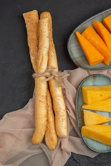 Verticale weergave van smakelijke plakjes kaas op een handdoek op een zwarte achtergrond