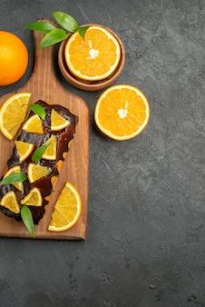 Verticale weergave van smakelijke taarten geheel en gesneden citroenen op snijplank op zwarte achtergrond