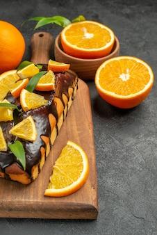 Verticale weergave van smakelijke taarten geheel en gesneden citroenen op snijplank op zwarte tafel