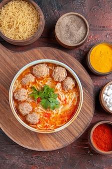 Verticale weergave van tomatengehaktballetjessoep met noedels in een bruine kom en verschillende kruiden op donkere achtergrond