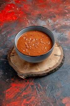 Verticale weergave van tomatensoep in een blauwe kom op een bruin houten dienblad op gemengde kleurentafel