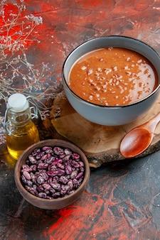 Verticale weergave van tomatensoep in een blauwe kom op een houten dienblad bonen olie fles op gemengde kleurentafel Gratis Foto