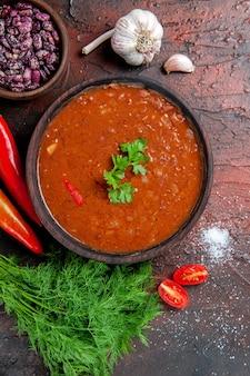 Verticale weergave van tomatensoep in een bruine kom en verschillende kruiden knoflook citroen op gemengde kleurentafel
