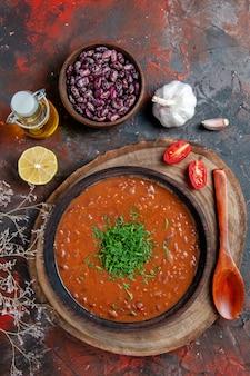 Verticale weergave van tomatensoep in een bruine kom olie fles bonen en lepel op gemengde kleurentafel