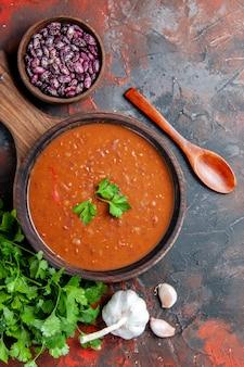 Verticale weergave van tomatensoep op een bruine snijplank op een achtergrond van gemengde kleur