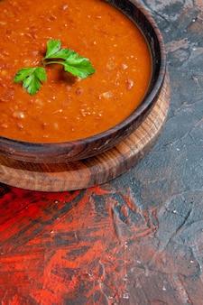 Verticale weergave van tomatensoep op een bruine snijplank op een gemengde kleurentafel