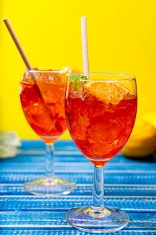 Verticale weergave van twee glazen van de aperol spritz-cocktail met munt-sinaasappelbladeren op een blauwe tafel