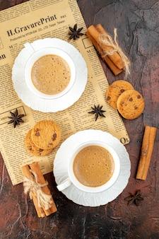 Verticale weergave van twee kopjes koffiekoekjes, kaneellimoenen op een oude krant op een donkere achtergrond