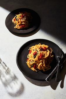 Verticale weergave van twee platen van spaghetti op een witte ondergrond